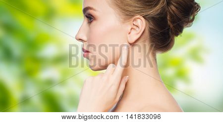 health, people, eco and beauty concept - beautiful young woman pointing finger to her ear over green natural background