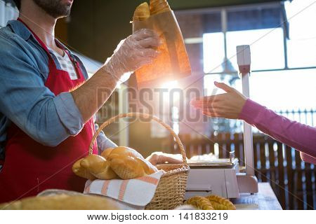 Staff giving packet bread to customer in supermarket