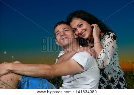 couple sit on grass and embrace on country outdoor, dark night sky, love concept, romantic young adult people