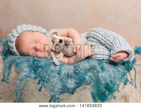beautiful newborn baby in knitted costume with hat sleeping on woolen blanket in basket