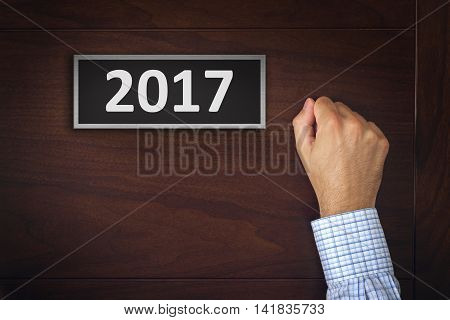 New year resolutions businessman knocking on the office door with number 2017.