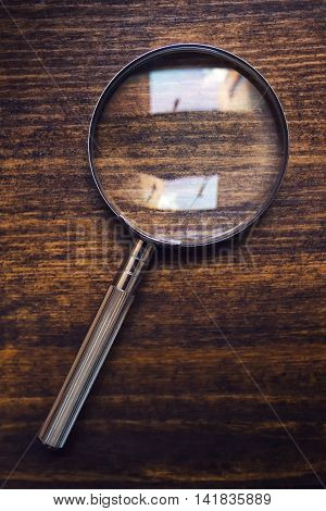 Loupe magnifying glass on wooden desk top view concept of searching and investigating