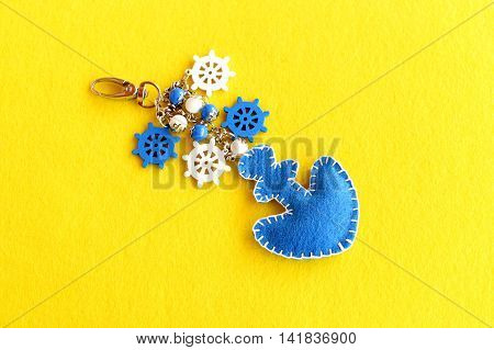 Felt anchor key chain decorated with beads and small decorative ship wheel. Beautiful keychain for car or beach bag isolated on yellow felt background. Charm accessory. Summer DIY idea