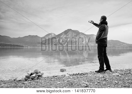Tall Man Hold Cellphone, Take Photo Of Autumn Mountain Lake Scenery