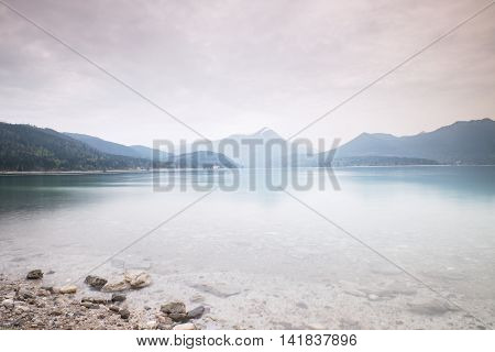 Cloudy Sunset At Mountain Lake. Stony Beach And Dark Mountains
