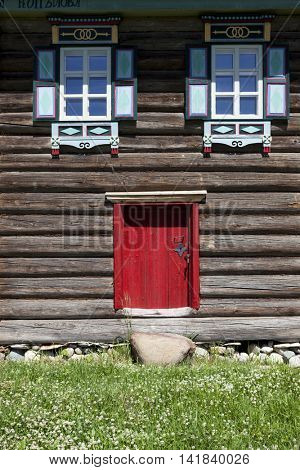 Red old door and window on the wooden wall of a village house. Excellent background in rustic style