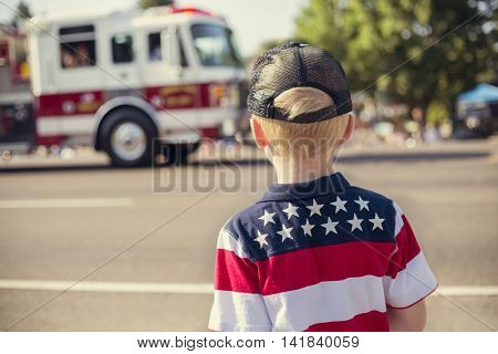 Kids watching an Independence Day Parade and a ambulance drives by