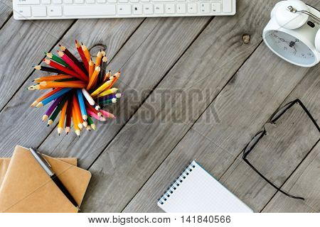 Many different colored pencils on wooden desktop with white keyboard alarm clock notepad glasses and pen. Focus on pencils. Top view with copy space