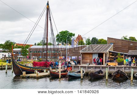 Roskilde Denmark - July 23 2015: Replicas of ancient boats and visitors outside the Viking Ship Museum