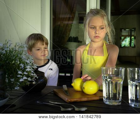 cute kids preparing lemonade in a glass jar