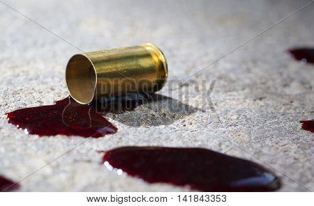 Blood around a single empty handgun casing on concrete
