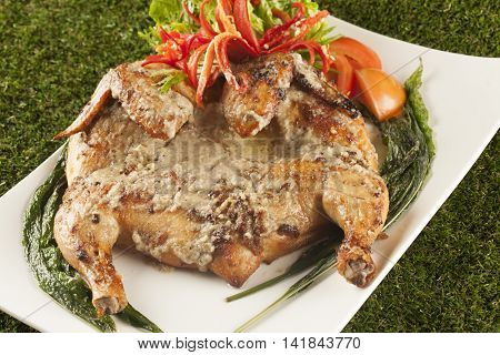 Ayam Kuzi fried chicken with chili tomatoes and lettuce on white plate