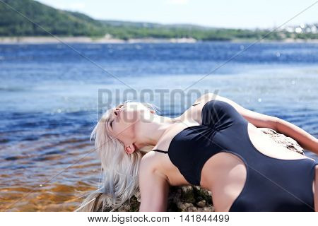 blonde in black bathing suit lying on his back shore of gulf