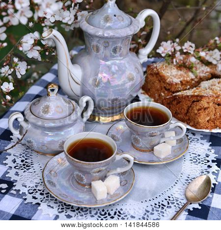 Still life with old tea set and home cake on white napkin, afternoon tea in the spring garden