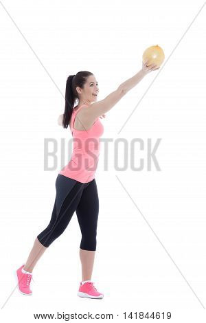 Fit woman holding a pomelo in one hand while posing