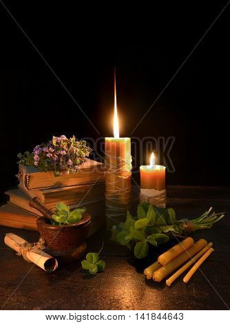Vertical still life with two burning candles, four leaf clover, book and manuscript scrolls on black, saint patricks day image