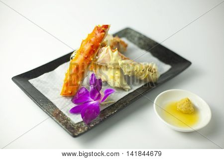Fried lobster claws on black plate with wasabi sauce on white background
