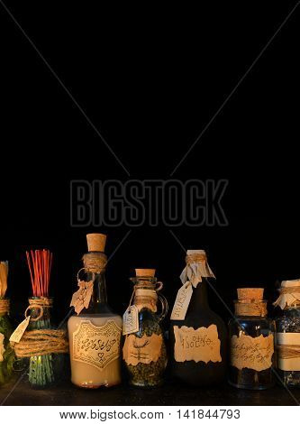 Vertical still life with witch bottles on black. Halloween or homeopathic image. Signs on labels are not foreign text, these letters are imaginary, fictional symbols.