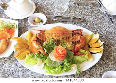 Curry crab with lettuce sliced eggplant chili and lemon sauce on white plate