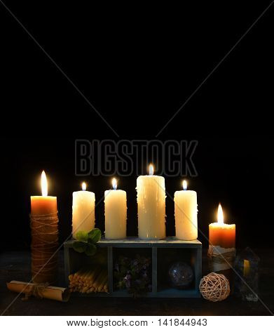 Vertical Halloween background with burning candles and magic objects on black