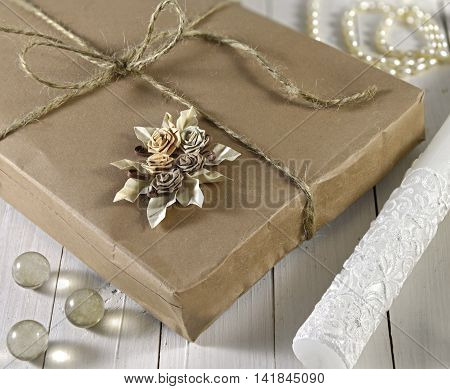 Close up of vintage gift box in wrapped brown paper on wooden planks