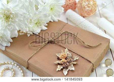 Close up of gift in brown wrapped paper with beautiful white flowers and trinkets