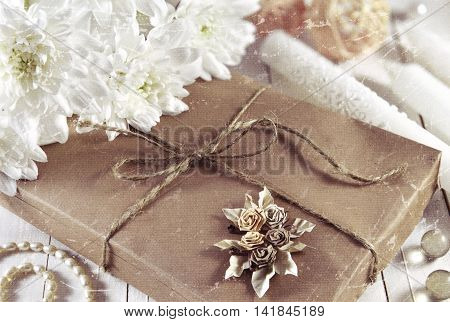Vintage still life with gift box in brown wrapped paper, jewelry, trinkets and white flowers, filtered and textured image
