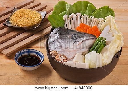 Hot pot of salmon head with mushroom carrot tofu cabbage and dried noodle on wooden table