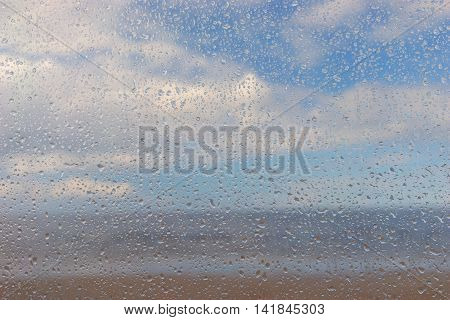 Raindrops on the film against the backdrop of the beach and blue sky with white clouds