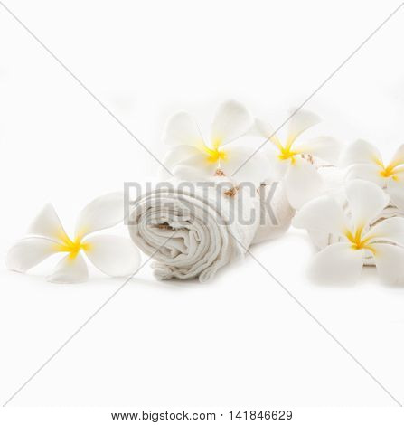 Spa set with towel and frangipani flower isolated on white