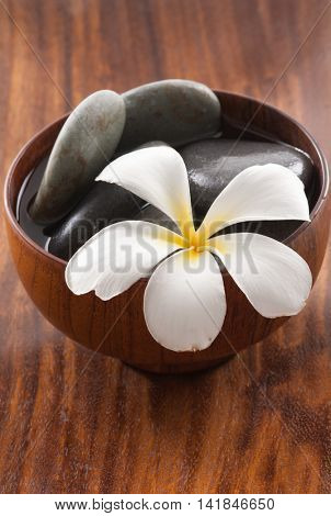 white flower,frangipani tropical ,stone,o in bowl on brown wooden,for spa