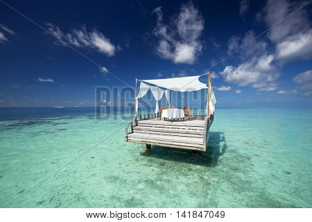 Oasis restaurant table among the sea with blue sky