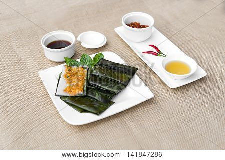 Vietnamese steamed rice pancake with shrimp or banh nam Hue on white plate with soyal sauce