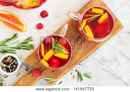 Red homemade fruit and berry tea with rosemary. Top view, space for text. Selective focus