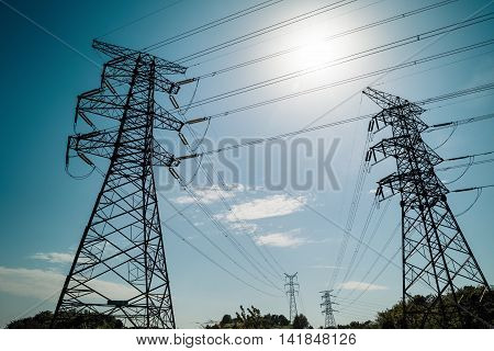 high voltage power transmission tower against a blue sky