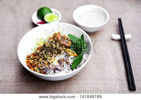 Vietnamese rice vermicelli with fried clams in white bowl with herbs and lemon