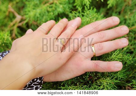Young couple holding hands outdoors. Wedding day.