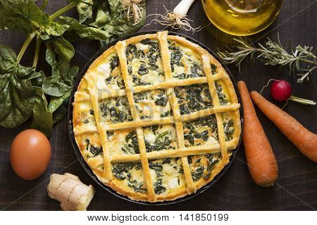 Vegetarian pie with ingredients on a black wooden background