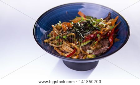 Udon with beef and vegetables in blue chinese bowl on white background