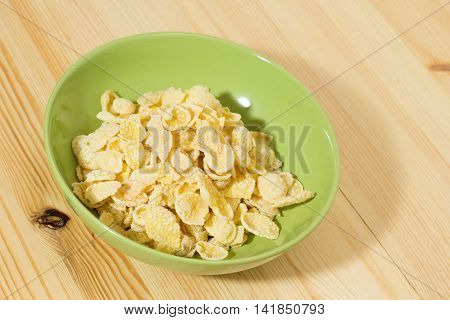 A bowl of Corn flakes on wooden table