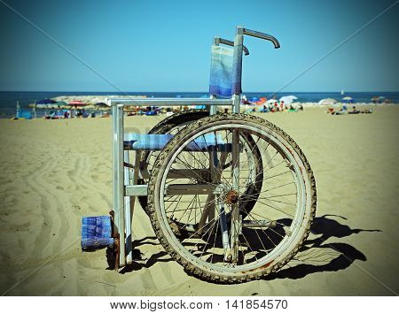 Wheelchair On The Sand Beach Near The Sea