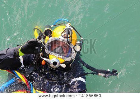 diver in the water in a diving suit and helmet ready to dive and showing sign ok