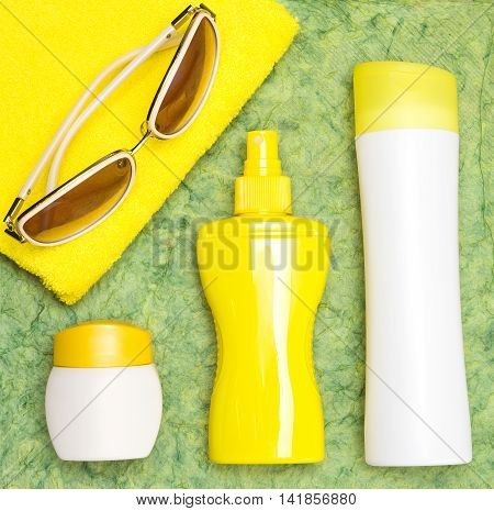 Cosmetic sunscreen products for face and body skin care towel and sunglasses. Lotion, spray and cream. Cosmetics containing sun protection factor