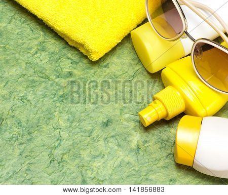 Cosmetic sunscreen products for face and body skin care towel and sunglasses. Lotion, spray and cream. Cosmetics containing sun protection factor. Copy space