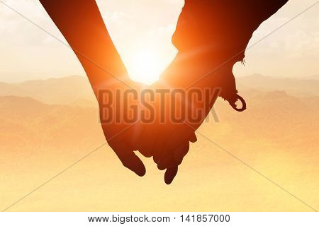 silhouettes on sunset of loving couple holding hands while walking at on Mount stacked.