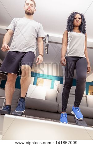 Young Couple He Trains With The Step Machine At Home
