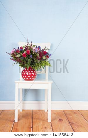 mixed bouquet flowers on chair at blue background