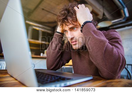 Stressful upset desperate handsome curly man in brown sweetshirt working using laptop and having headache