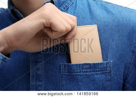 Man putting wallet in shirt pocket, closeup