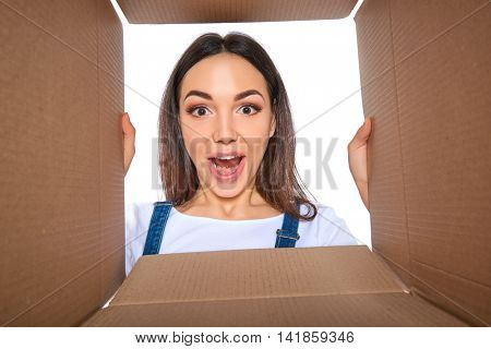 Happy girl opening postal package. Excited young woman holding cardboard box and looking inside. Gift, present, delivery, shipment, sale concept.